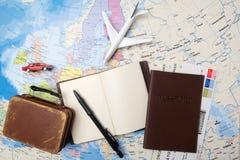 Reise, Reiseferien, Tourismusmodell - nahes hohes Anmerkungsbuch, Koffer, Spielzeugflugzeug auf Karte lizenzfreies stockbild