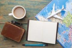 Reise, Reiseferien, Tourismusmodell - nahes hohes Anmerkungsbuch, Koffer, Spielzeugflugzeug und touristische Karte auf Holztisch lizenzfreie stockbilder