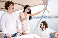 Reise, seatrip, Freundschaft und Leutekonzept - Freunde, die auf Yachtplattform sitzen lizenzfreies stockfoto
