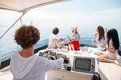 Reise, seatrip, Freundschaft und Leutekonzept - Freunde, die auf Yachtplattform sitzen lizenzfreies stockbild