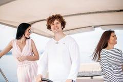Reise, seatrip, Freundschaft und Leutekonzept - Freunde, die auf Yachtplattform sitzen stockbild