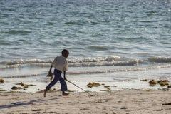 Reise um Tansania Wenig Junge, der entlang die Küste läuft stockfoto