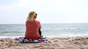 Reise und Ferien Erwachsene Blondine sitzen auf dem Meer und entspannen sich stock video