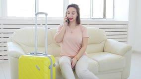 Reise, Reise und Ferienkonzept - Frau mit gelbem Koffer wartet auf das Taxi stock footage