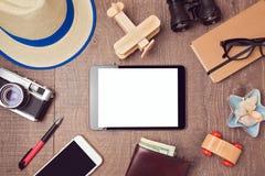 Reise- und Ferienkonzepthintergrund mit digitalem Tablettenspott oben und Gegenständen Ansicht von oben Stockfotografie