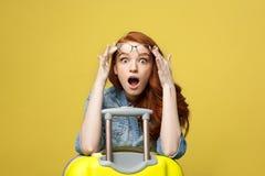 Reise-und Lebensstil-Konzept: Porträt eines entsetzten Mädchens im Jeanskleid mit dem Koffer, der die Kamera vorbei lokalisiert b stockfotografie