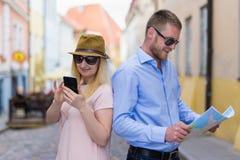 Reise- und Tourismuskonzept - glückliche Touristen mit Stadtplan und Inspektion lizenzfreie stockfotografie