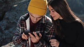 Reise zu den Bergen Schönes Paar in der Liebe sitzt auf dem Felsen und mit Karte auf Smartphone Mann zeigt Freundin stock footage