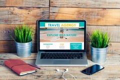 Reisebürowebsite auf einem Laptopschirm Öffnen Sie Einsteigeloch mit Ablichtung nach innen auf checkered Oberfläche stockbild