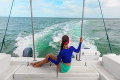 Reisebootsexkursionsausflug-Frauentourist, der auf Plattform des Motorbootkatamarans, Sommer Floridas, USA sich entspannt stockfoto