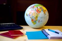 Reiseeinzelteile, blauer Notizblock, Stift, PC, Kugel auf hölzernem Hintergrund Lizenzfreies Stockfoto