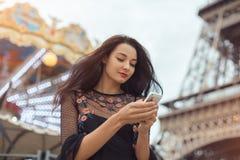 Reisefrau, die Smartphone nahe dem Eiffelturm und dem Karussell, Paris verwendet stockbilder