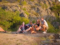 Reisegesellschaft, die auf einem natürlichen Hintergrund sich entspannt Freunde nähern sich Kamin mit einer Gitarre Kampierendes  lizenzfreie stockfotos