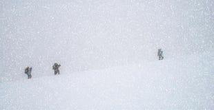 Reisegesellschaftstrekking in den Bergen im Schnee blizzar Stockbilder