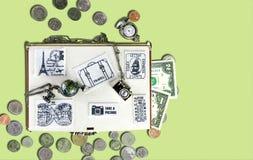 Reisekonzept: Hölzerner Reisekasten mit Aufklebern des Gewebes, Banknoten und Münzen, Uhren, Metallanhänger in Form Stockfotografie