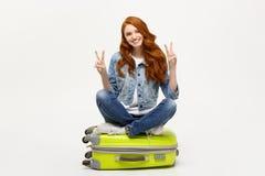 Reisekonzept: lächelnde kaukasische Frau der Junge, die auf dem Koffer zeigt zwei Finger stationiert in weißem mit buntem Kranz a stockfotografie