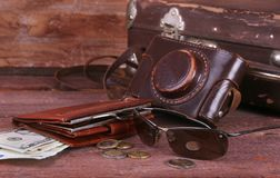 Reisekonzept mit Weinlesekoffer, Sonnenbrille, alter Kamera, Velourslederstiefeln, Kasten für Geld und Pass auf Bretterboden Stockbild