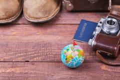 Reisekonzept mit Weinlesekoffer, Sonnenbrille, alter Kamera, Velourslederstiefeln, Kasten für Geld und Pass auf Bretterboden Lizenzfreies Stockfoto