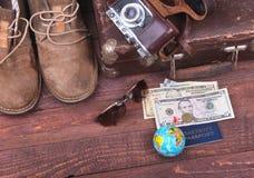 Reisekonzept mit Weinlesekoffer, Sonnenbrille, alter Kamera, Velourslederstiefeln, Kasten für Geld und Pass auf Bretterboden Stockbilder