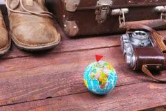 Reisekonzept mit Weinlesekoffer, Sonnenbrille, alter Kamera, Velourslederstiefeln, Kasten für Geld und Pass auf Bretterboden Stockfotos
