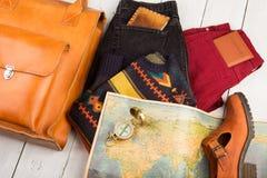 Reisekonzept, Tasche, Schuh, Jeans, geographische Karte, Pass, Kompass, Geldbeutel auf weißem Holztisch lizenzfreie stockfotos