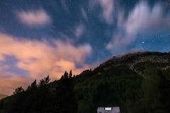 Reisemobil unter Mondschein, sternenklarem Himmel und unscharfer Bewegung bewölkt sich auf den majestätischen Alpen Tätigkeiten i Lizenzfreie Stockfotografie