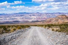 Reisen auf eine Staubstraße durch ein entlegenes Gebiet Nationalparks Death Valley; Berge, blauer Himmel und weiße Wolken in stockfoto