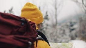 Reisen in die Berge Junger Mann, der die gelbe Winterkleidungs-Holdingkarte im Wald geht bedeckt mit Schnee trägt stock video