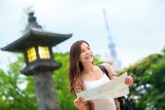 Reisen Sie in Tokyo - asiatische touristische Frau mit Karte Stockfotografie