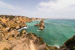 Reisen Sie zu erstaunlichen Felsenklippen mit Seehöhlen auf sandigem Camilo-Strand im bunten sonnigen blauen Himmel stockfotos