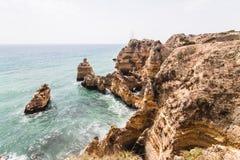 Reisen Sie zu erstaunlichen Felsenklippen mit Seehöhlen auf sandigem Camilo-Strand im bunten sonnigen blauen Himmel lizenzfreie stockfotos