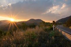 Reisen Sun stellt hinter die Berge ein, die Straße glänzen Stockbild