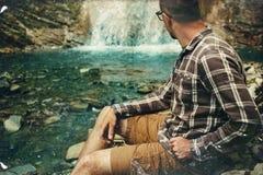 Reisend-Forscher Sitting And Looks auf Wasserfall Reise, die Bestimmungsort-Erfahrungs-Lebensstil-Konzept wandert lizenzfreies stockbild