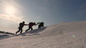Reisende in der Arktis auf einem Hügel in den hellen Strahlen der Sonne Teamwork-Wunsch zu gewinnen Bergsteiger klettern zur Spit stock footage