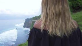 Reisende Frau auf Klippengebirgs- und -wasserwellenhintergrund auf Ozeanufer Aufpassender Klippenberg der jungen touristischen Fr stock video footage