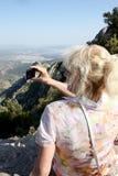 Reisende Frau, die auf den Felsen und den Fotografien sitzt Stockbild