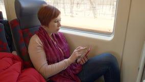 Reisende Frau, die den Smartphone sitzt auf Fensterhintergrund in beweglichem Zug schaut stock footage