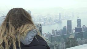 Reisende Frau, die Hong Kong-Stadtpanorama von Höchst-Victoria aufpasst Touristische Frau, die Panoramablick Hong Kong-Stadt scha stock footage
