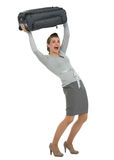 Reisende Frau, die Koffer über Kopf anhebt Stockbilder