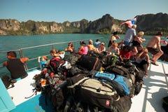 Reisende gehen auf eine Fähre über dem Meer zu den Inseln mit großen Rucksäcken Lizenzfreies Stockfoto