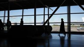 Reisende im Flughafen gehend zur Abfahrt durch Rolltreppe vor Fenster, Schattenbild stock video footage