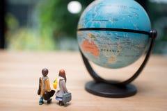 Reisende Konzepte Zwei von Miniaturminizahlen mit Tasche Stockfotografie