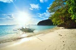 Reisende treffen den Sonnenuntergang auf einem wilden Strand gegen die Inseln von Stockbilder