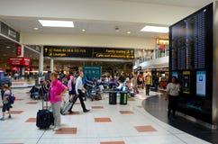 Reisende und Leute Englands am Flughafen-Abfahrtaufenthaltsraum Londons Gatwick mit Fluganzeige Lizenzfreies Stockbild