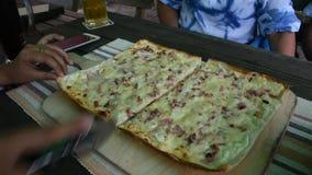 Reisende, welche die Leute, die Pizza schneiden dünn, für verkrusten, essen am Restaurant stock video footage
