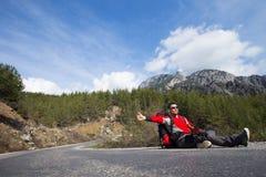 Reisenden per Anhalter fahrend, versuchen Sie, Auto auf der Gebirgsstraße zu stoppen Lizenzfreie Stockfotografie