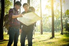 Reisender übertreffen des jungen Mann-zwei mit Rucksack, die Betrachtenentspannende karte Lizenzfreie Stockfotografie