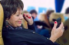 Reisender aufpassender Film der alten Frau mit Handy Lizenzfreies Stockfoto