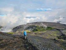 Reisender, der die Frauen gehen auf Straße in Island-Hochländern mit dem schweren Rucksack Reise-Lebensstilfreiheits-Konzeptabent stockfoto