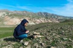 Reisender, der einen Kompass in den Bergen hält Lizenzfreies Stockfoto